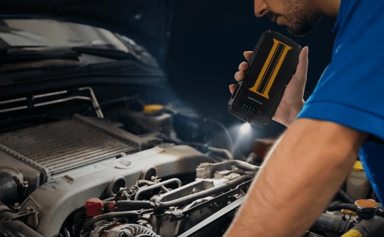 Gambar ini menunjukkan seorang pria sedang memeriksa mesin Mobil di malam hari dengan memegang senter