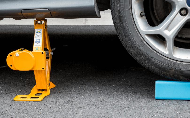 Gambar ini menunjukkan sebuah dongkrak warna kuning diletakkan di bawah Mobil dekat ban