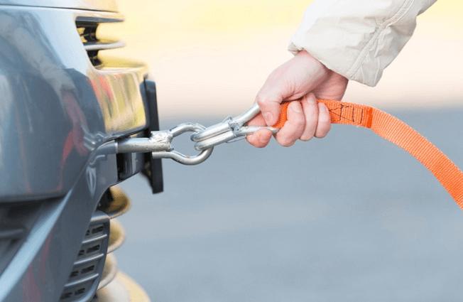 Gambar ini menunjukkan sebuah tangan memegang tali di pasangkan di bagian belakang kendaraan