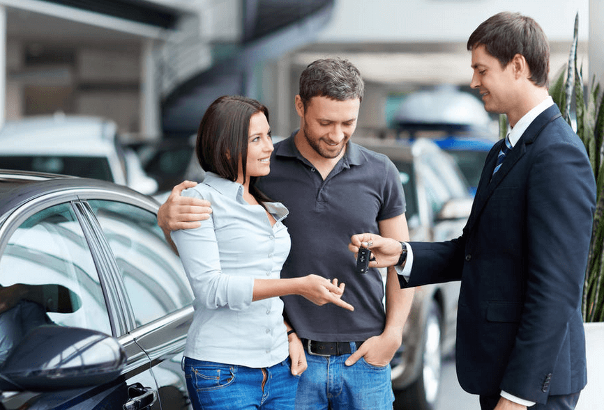 Gambar ini menunjukkan 3 orang 2 pria satu wanita berdiri di samping Mobil warna hitam