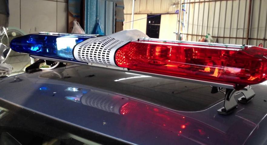Gambar ini menunjukkan lampu rotator warna merah dan biru dipasangkan di atas Mobil