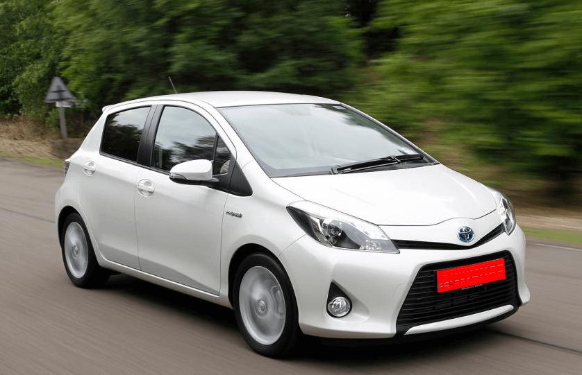 Gambar ini menunjukkan Mobil Toyota warna putih sedang melaju di jalanan