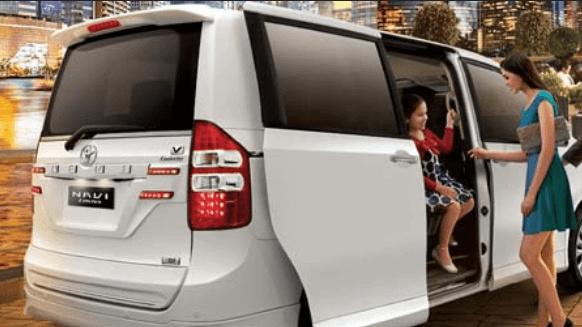 Gambar ini menunjukkan Toyota NAV1 warna putih dan terdapat seorang wanita akan masuk ke dalamnya