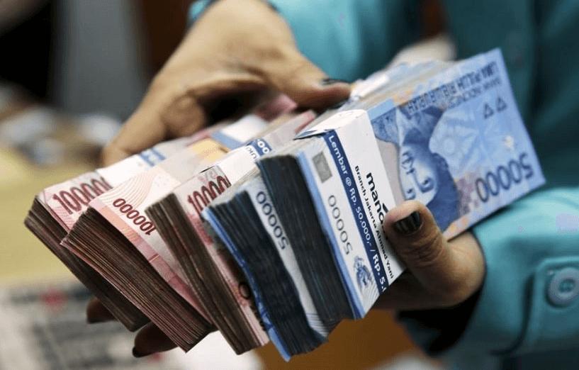 Gambar ini menunjukkan tumpukan uang lembaran 50.000 dan 100.000 dipegang dengan tangan