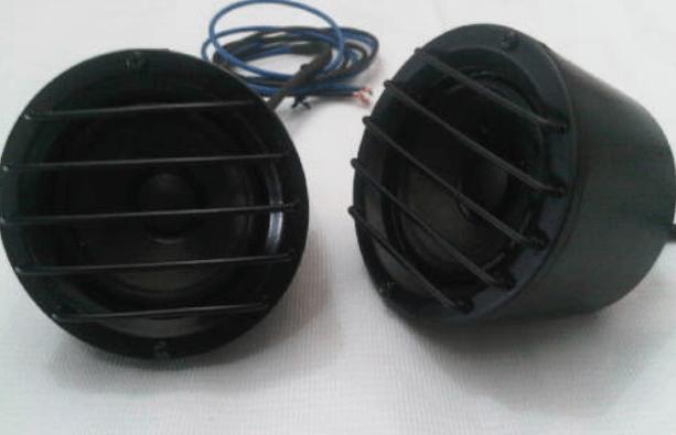 Gambar ini menunjukkan 2 buah speaker warna hitam dan terlihat sedikit gulungan kabel di belakangnya