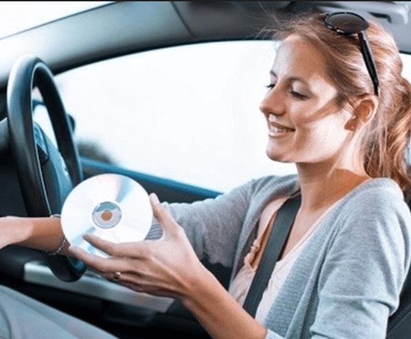 Gambar ini menunjukkan seorang wanita memegang kaset cd di dalam Mobil