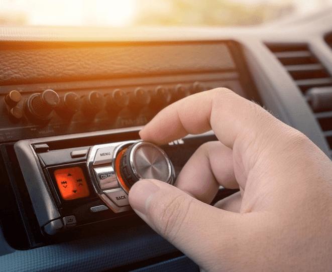 Gambar ini menunjukkan sebuah tangan memegang panel audio di dashboard Mobil