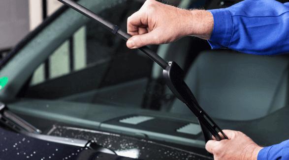 Gambar ini menunjukkan sebuah tangan memegang wiper Mobil dan dibuatnya berdiri