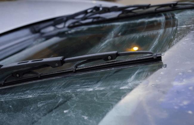 Gambar ini menunjukkan wiper Mobil sedang bekerja membersihkan kotoran pada kaca depan Mobil