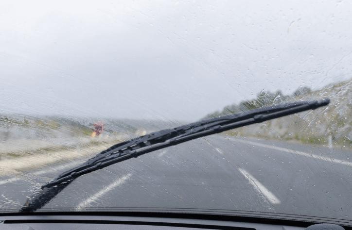 Gambar ini menunjukkan wiper Mobil bekerja mengusap kaca dpean Mobil yang basah