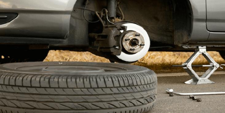 Gambar ini menunjukkan ban mobil yang tergeletak dengan mobil sedanh di dongkrak
