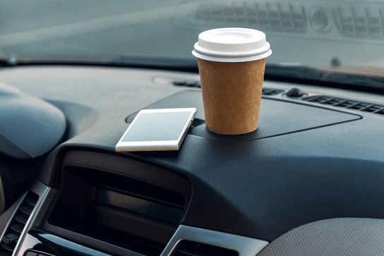 Gambar ini menunjukkan kopi dan hanphonedalam notol yang diletakkan di atas dasbor