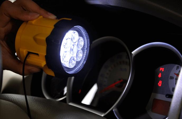 Gambar ini menunjukkan sebuah tangan memegang senter disorotkan pada speedometer