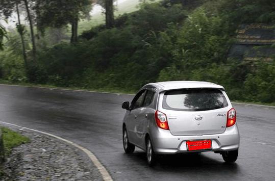 Gambar ini menunjukkan sebuah mobil sedang melintasi tikungan di jalan