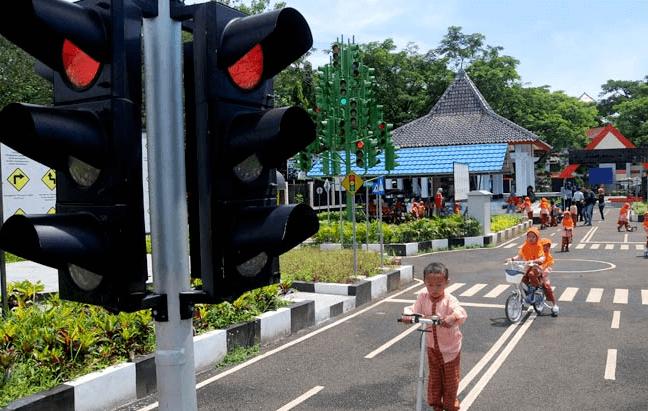 Gambar ini menunjukkan lampu lalu lintas menyala merah dan terdapatbeberapa anak di jalan
