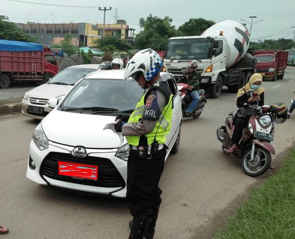 Gambar ini menunjukkan seorang Polisi membawa kertas berdiri di depan mobil warna putih