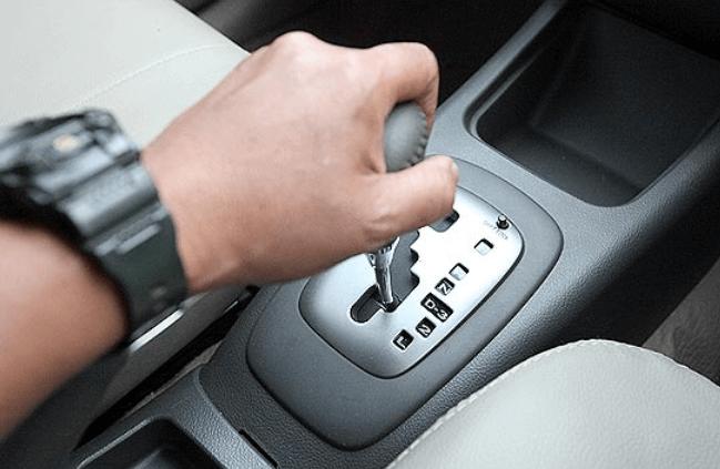 Gambar ini menunjukkan sebuah tangan sedang memegang tuas transmisi mobil matic