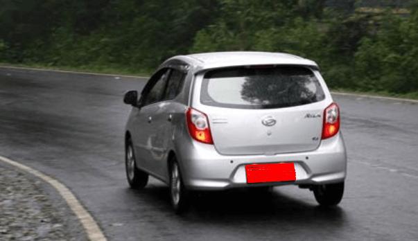 Gambar ini menunjukkan sebuah mobil melaju di jalan basah tampak bagian belakang
