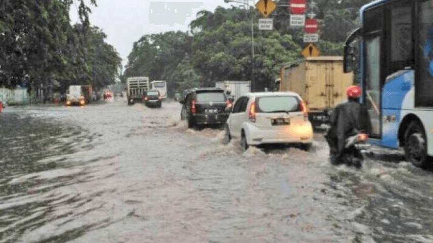 Gambar ini menunjukkan beberapa mobil dan bus serta kendaraan lain sedang melaju di jalanan yang terendam banjir