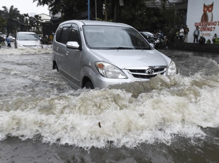 Gambar ini menunjukkan sebuah mobil sedang menerjang banjir dan terdapat mobil lain di belakangnya