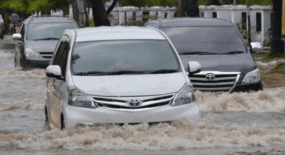 Gambar ini menunjukkan 3 buah mobil 2 warna hitam dan 1 warna hitam sedang melintasi genangan air di jalan