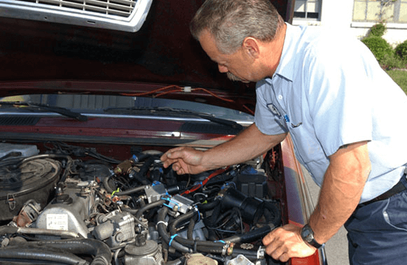 Gambar ini menunjukkan seorang bapak-bapak memegang dan melihat komponen mesin pada mobil
