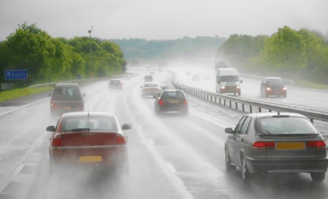 Gambar ini menunjukkan beberapa mobil melaju di jalanan dalam kondisi hujan