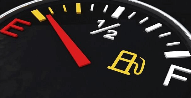 Gambar ini menunjukkan indikator bahan bakar dengan jarum merah serta tulisan E dan F