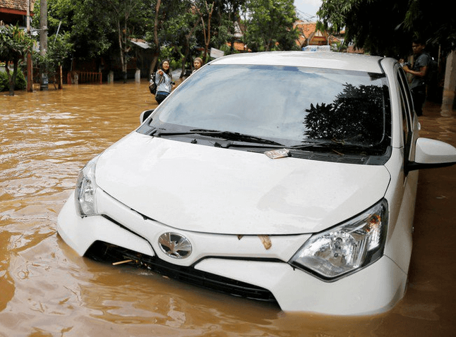 Gambar ini menunjukkan sebuah mobil warna putih dalam kondisi terdendam banjir