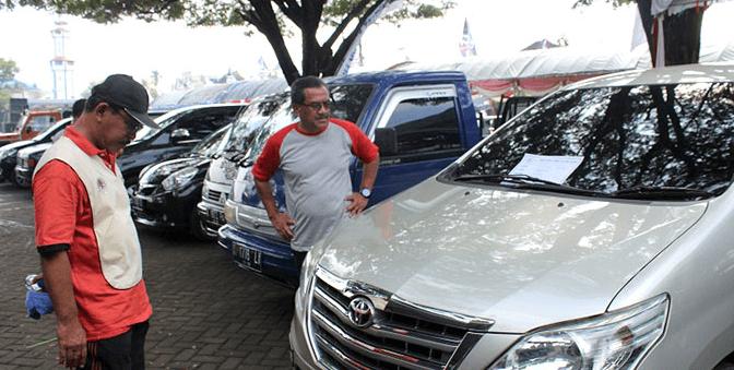 Gambar ini menunjukkan 2 orang pria berdiri di depan mobil warna silver