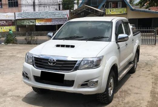 Gambar ini menunjukkan mobil Toyota Hilux warna putih terlihat bagian depan