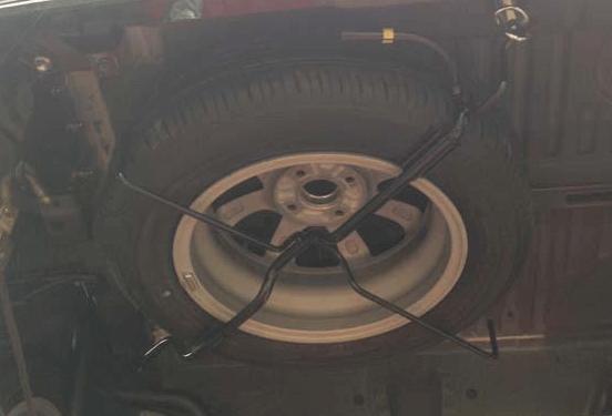 Gambar ini menunjukkan ban serep milik Toyota Calya yang diletakkan di bagian belakang bawah kendaraan
