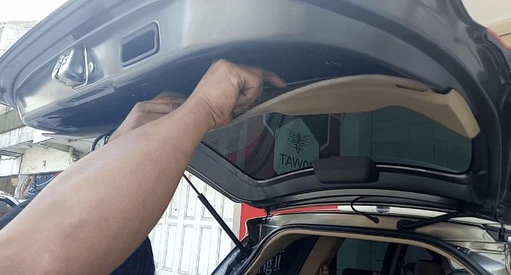 Gambar ini menunjukkan sebuah tangan memegang komponen pada pintu belakang mobil bagian dalam