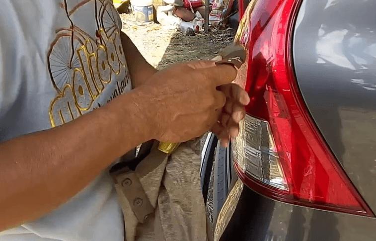 Gambar ini menunjukkan seseorang memegang sebuah alat di belakang Mobil Toyota Avanza yang terlihat bagian lampunya