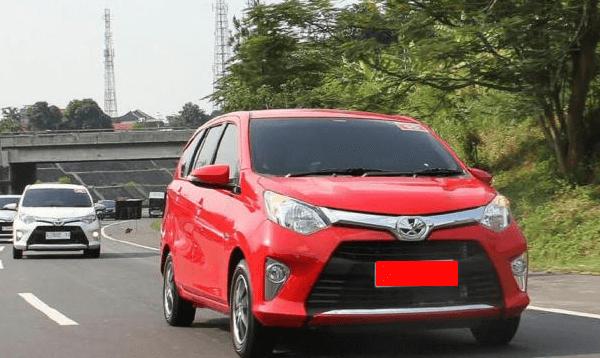 Gambar ini menunjukkan Mobil Toyota Calya warna merah melaju di jalan dan terdapat beberapa mobil di belakangnya