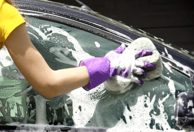 Gambar ini menunjukkan sebuah tangan memegang busa ditempelkan pada bodi mobil yang berbusa