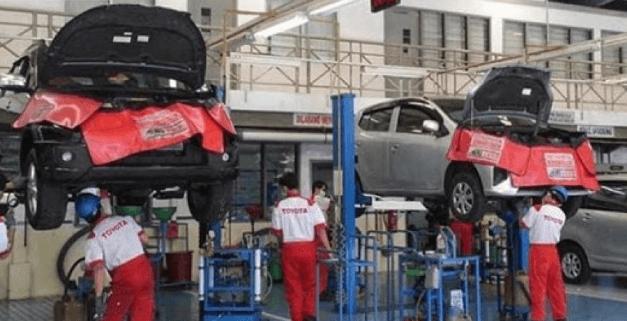 Gambar ini menunjukkan 2 buah mobil sedang di servis di bengkel resmi Toyota dan terdapat beberapa mekanik di bawahnya