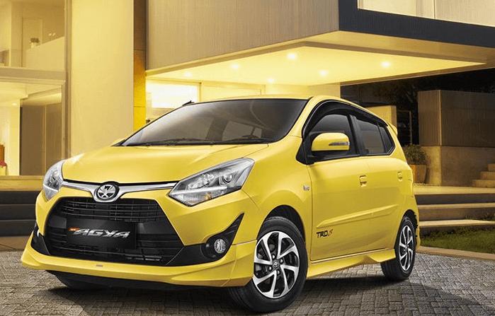 Gambar ini menunjukkan mobil Toyota Agya warna kuning tampak bagian depan dan samping
