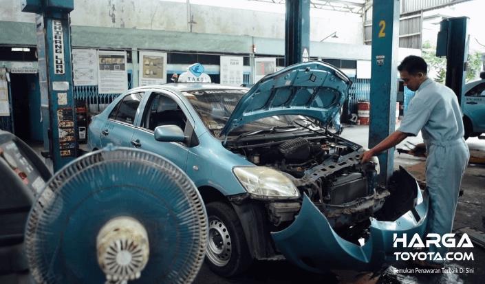 Gambar ini menunjukkan mobil taksi warna biru sedang dilakukan pengecekan pada mesinnya