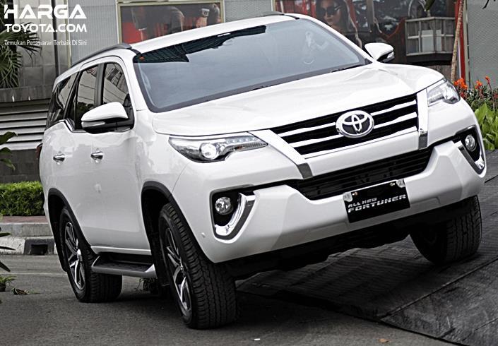 Gambar ini menunjukkan Toyota Fortuner warna putih tampak depan sedang melintasi jalanan miring
