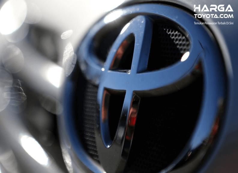 Gambar ini menunjukkan logo mobil Toyota pada sebuah kendaraan