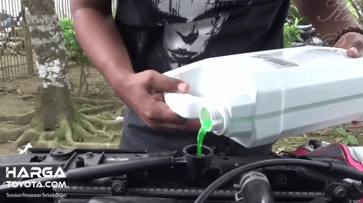 Gambar ini menunjukkan seseorang sedang mengisi air radiator pada mobil