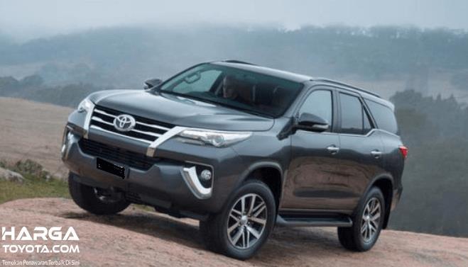 Gambar ini menunjukkan Toyota Fortuner warna hitam sedang melaju di medan menanjak