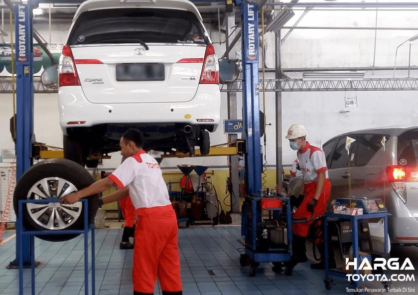 Gambar ini menunjukkan bengkel resmi Toyota dan terdapat beberapa mekanik sedang melakukan pekerjaannya