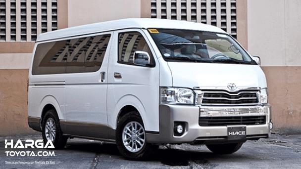 Gambar ini menunjukkan sebuah mobil Toyota Hiace sedang terparkir di samping dinding tampak bagian depan