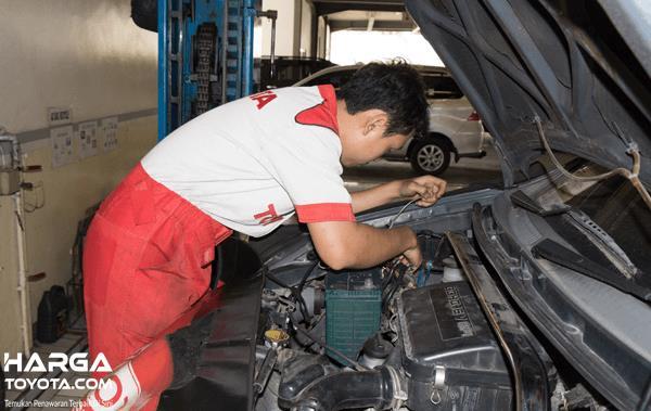 Gambar ini menunjukkan seorang mekanik sedang memperbaiki mesin Toyota Avanza