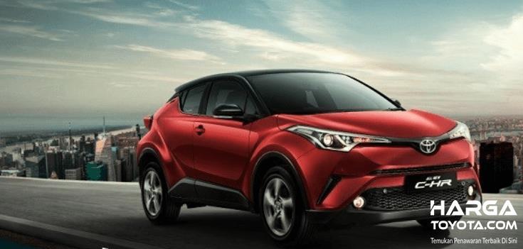 Gambar ini menunjukkan Mobil Toyota C-HR warna merah tampak bagian samping dan depan