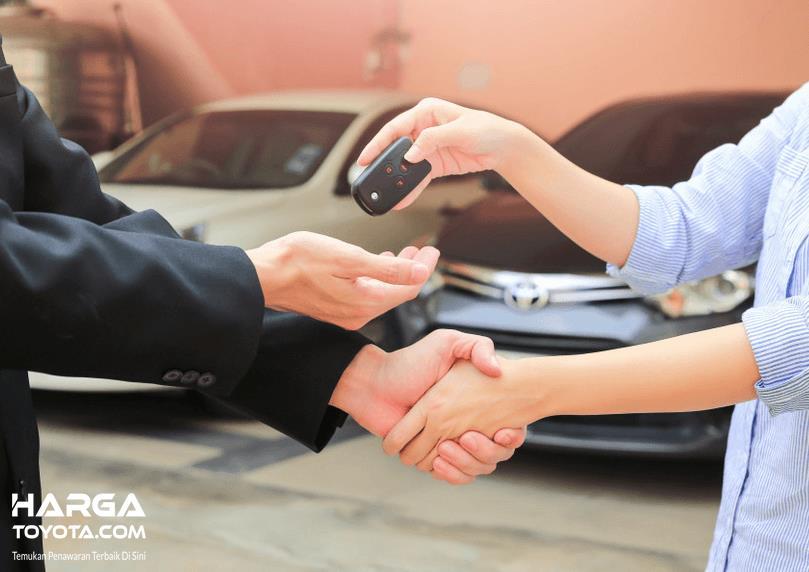 Gambar ini menunjukkan 2 buah tangan bersalaman dan menyerahkan kunci mobil