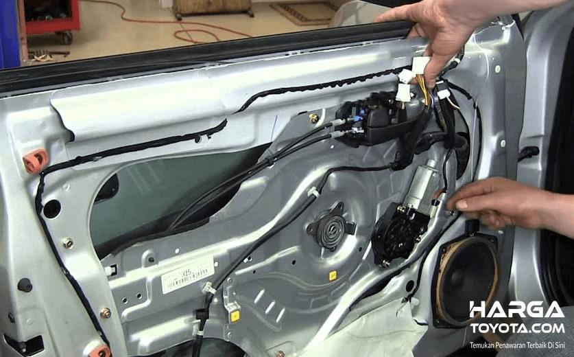 Gambar ini menunjukkan mekanisme power window yang sedang diperbaiki dengan tangan