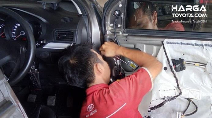 Gambar ini menunjukkan seseorang berbaju merah sedang membongkar power window pada pintu mobil